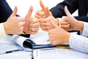 Three people holding their thumbs up meaning a great business plan